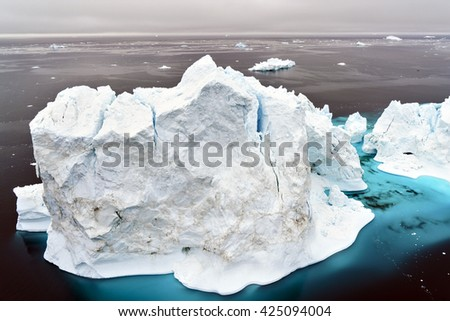 Arctic Icebergs Greenland in the arctic sea. You can easily see that iceberg is over the water surface, and below the water surface. Sometimes unbelievable that 90% of an iceberg is under water - stock photo