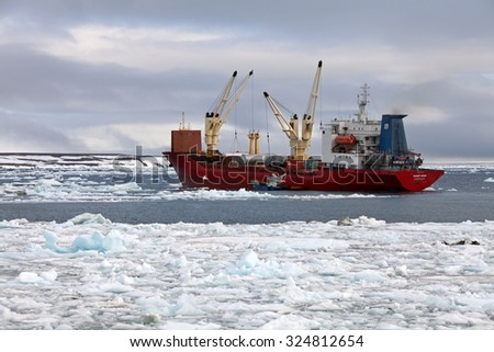 ARCTIC OCEAN, RUSSIA - July 24, 2015:  Cargo ship â??Polar Kingâ?? delivering supplies. Summer in Arctic is very short and  all goods have to be delivered to remote polar settlements within this period   - stock photo