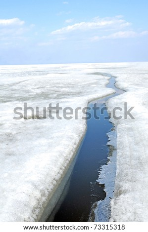arctic solid ice landscape with track of ice-breaker ship - stock photo
