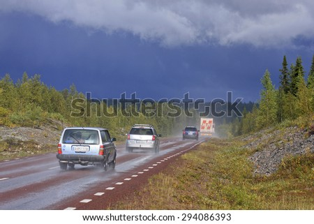 ARCTIC, SWEDEN ON AUGUST 30. Vehicle, cars on a highway after heavy rain on August 30, 2009 in Lapland, Sweden. Forests and rain ahead.