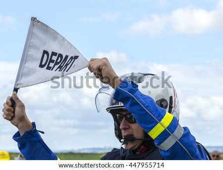 "ARDEVON, FRANCE- JUL 2: Unidentified French policeman holding the ""Start"" flag while launching the Tour de France at Km 0 in Ardevon,France on July 2,2016."