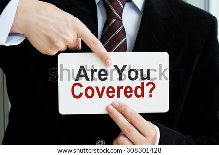 Are you Covered? Man holding a card with a message text written on it - stock photo