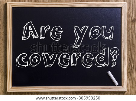 Are you covered? - New chalkboard with outlined text - on wood - stock photo