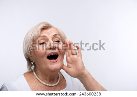 Are you getting the message. Closeup portrait of elderly woman putting her hand to mouth directing to copy space while standing against white background - stock photo