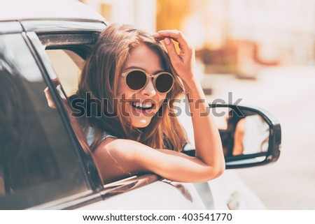 Are you going with me? Rear view of beautiful young cheerful women looking at camera with smile while sitting in her car