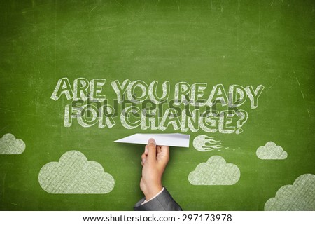 Are you ready for change concept on green blackboard with businessman hand holding paper plane - stock photo
