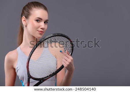 Are you ready to play. Portrait of beautiful young woman in sports clothing holding tennis racket and smiling while standing isolated over the grey background - stock photo