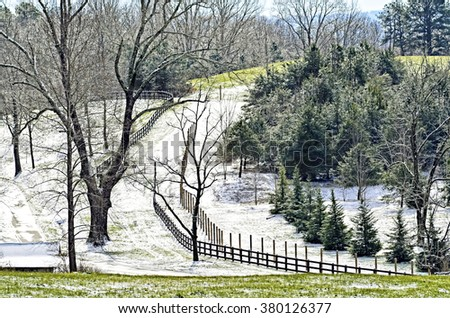Area of a pasture with a light dusting of snow on the ground.