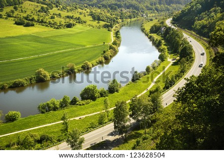 Areal view on Neckar river winding its way through a green valley in Germany