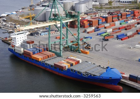 arel-view of a commercial container-port with ship, forklifts and oil-towers in background
