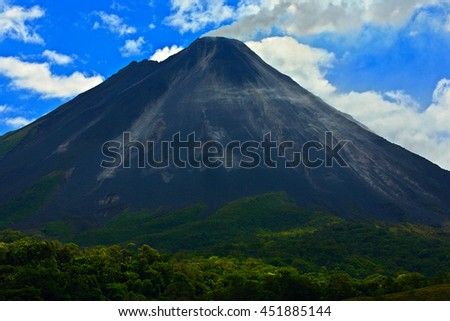 Arenal Volcano in Costa Rica. Volcano with exhalation and ash. Beautiful tropic landscape with volcano. Cone active volcano in Central America. Active Volcano Arenal with blue sky with clouds. - stock photo