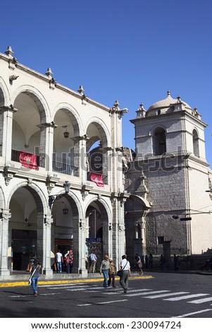 AREQUIPA, PERU - AUGUST 22, 2014: Paseo Portal de Flores and tower of Iglesia de la Compania at Plaza de Armas (main square) on August 22 2014 in the UNESCO World Cultural Heritage Site Arequipa, Peru - stock photo