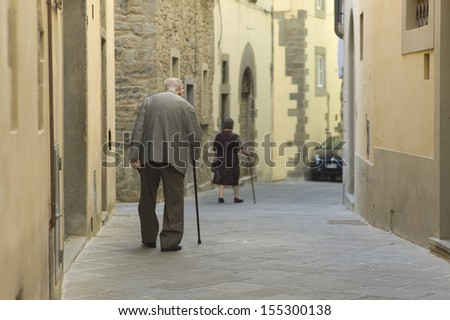 AREZZO, ITALY - SEPTEMBER 16: Old couple holding cane, walking along in street on September 16, 2013 in Arezzo, Italy - stock photo