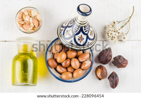 Argan Fruit on a wooden tabletop, Some fruit are without shell, other are in a Moroccan Tajine - stock photo