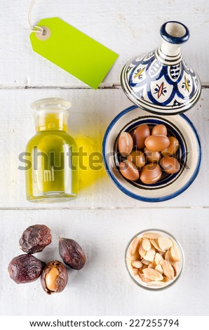 Argan fruits in different conditions (shell, nut and almond) with argan oil in a glass bottle.  - stock photo