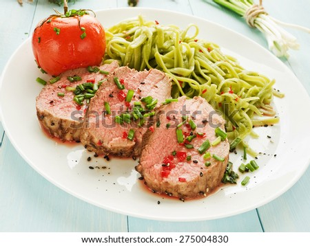 Argentinian Asado beef fillet with herbs, veggies and sauce. Shallow dof. - stock photo