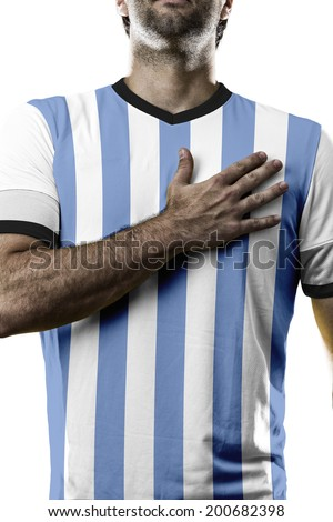 Argentinian soccer player, listening to the national anthem with his hand on his chest. On a white background. - stock photo