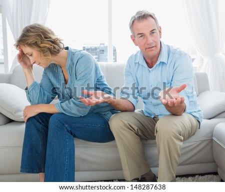 Arguing middle aged couple sitting on the couch with man gesturing at camera at home in the living room