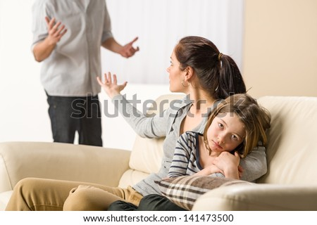 Arguing parents with upset little girl - stock photo