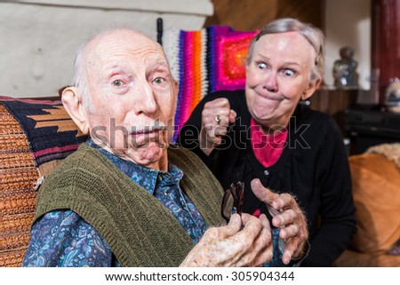 Arguing senior woman with clenched fist and confused husband - stock photo