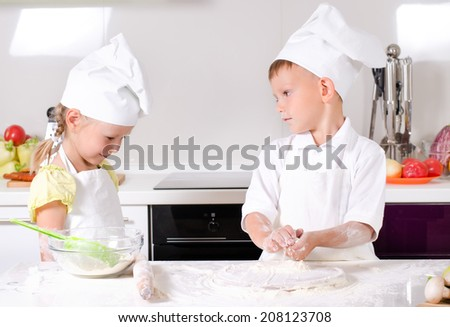 Arguments in the kitchen with a cute little girl in a cooks uniform admonishing a young boy in chefs uniform as they work together in the kitchen baking biscuits - stock photo