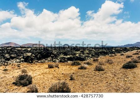 Arid area with volcanoes in Lanzarote island  - stock photo