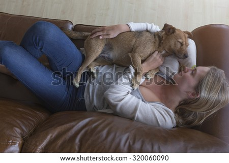 Ariel view of a woman cuddling her pet dog on a leather sofa.