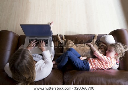 Ariel view of a woman using a laptop whilst her daughter is sleeping next to her, cuddling their pet dog. - stock photo