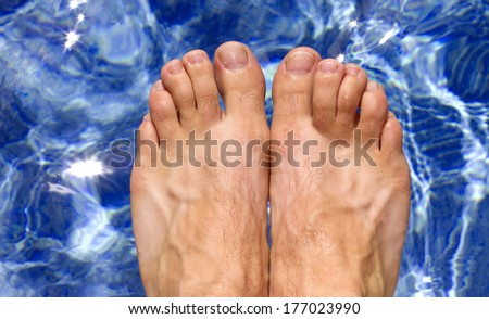 ariel view of mans feet as he is about to dive into a clear blue swimming pool - stock photo