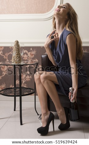aristocratic woman is sitting in elegant ambient on sofa with evening blue dress with a bottle of champagne in the hand and happy relaxed expression