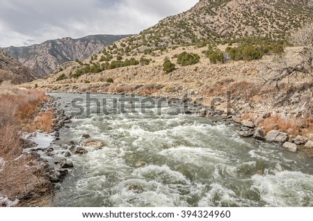 Arkansas River in Colorado running swiftly through the mountains on a winter day