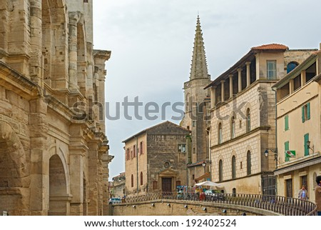 Arles, France - March 30: People walking around Old Roman Amphitheater and Collage Saint Charles tower at the background in Arles, France on March 30, 2014.