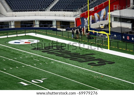 ARLINGTON - JAN 26: Unidentified individuals interviewing in the Steelers end zone of Cowboys Stadium in Arlington, TX - sight of the 2011 NFL Super Bowl XLV. Taken January 26, 2011 in Arlington, TX. - stock photo