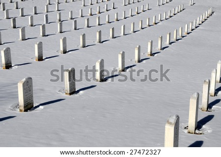 ARLINGTON - MARCH 3: Straight rows of graves at the Arlington National Cemetery after the biggest snowstorm of the winter March 3, 2009 in Arlington, Virginia. About 8 inches of snow fell in the morning before. - stock photo