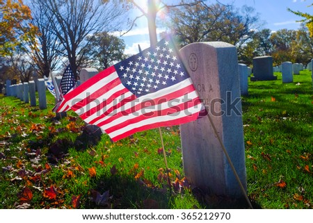 Arlington National Cemetery - Headstone and US National flag with lens flare - Washington DC, USA  - stock photo
