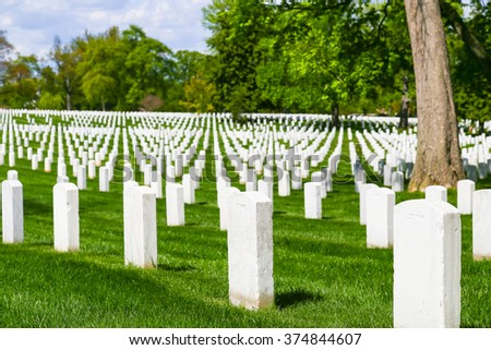 ARLINGTON, USA - MAY 2, 2015: White gravestones on the green lawn of Arlington National Cemetery.