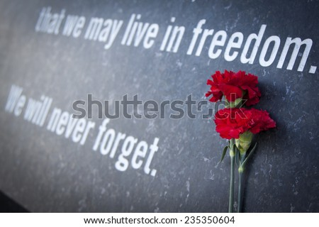 ARLINGTON, VA - SEPT 13, 2014: Red carnations laying against the granite wall of the Memorial Gateway entrance to the Pentagon Memorial dedicated to the victims of the September 11, 2001 attack. - stock photo