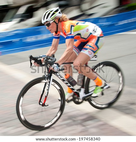 ARLINGTON, VIRGINIA - JUNE 8: A cyclist competes in the Crystal Cup elite women's race at the Air Force Cycling Classic on June 8, 2014 in Arlington, Virginia - stock photo