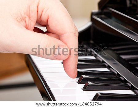 arm bent over the keyboard musical instrument