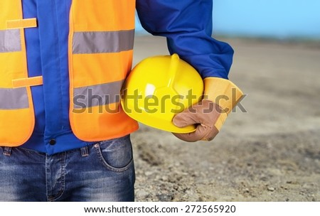 Arm. Builder with yellow helmet and working gloves on building site - stock photo