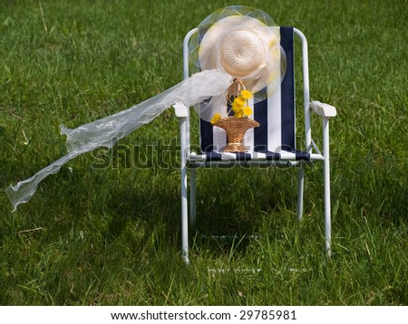 Arm-chair for a picnic, hat and basket with dandelions on a grass