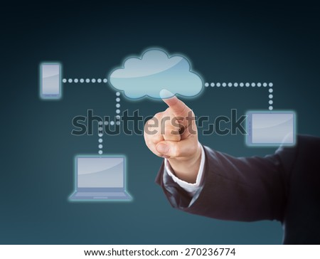 Arm in corporate suit is raising hand to push a cloud button within a touch screen interface. The cloud computing symbol is part of a network linking to cell phone, laptop and tablet computer icons. - stock photo