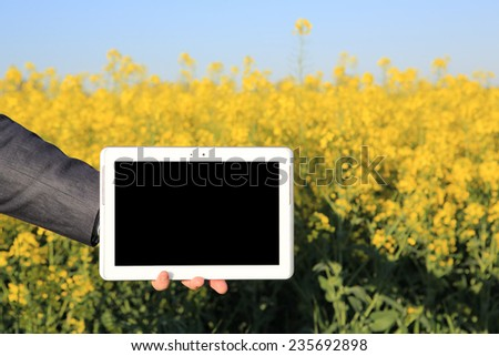 Arm of a business man holding a digital tablet in front of a canola field. The digital tablet is blank and ideal for inserting charts or text.  - stock photo