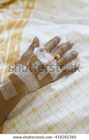 Arm of a female patient in the hospital with an iv intravenous drip - stock photo