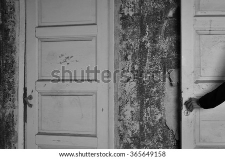 Arm with doll hand on the door of a haunted house. Black and white. - stock photo