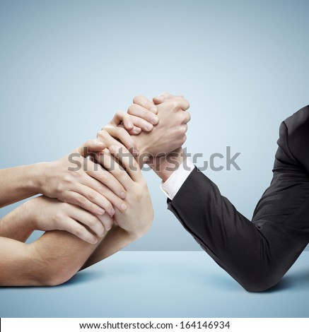 arm wrestling: businessman in opposition with many hands on blue background
