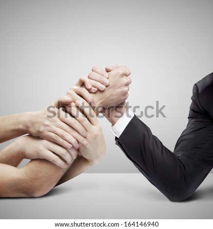 arm wrestling: businessman in opposition with many hands on gray background