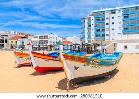 ARMACAO DE PERA BEACH, PORTUGAL - MAY 17, 2015: typical fishing boats on beach in Armacao de Pera coastal town with apartment building in background. Algarve region is popular holiday destination. - stock photo