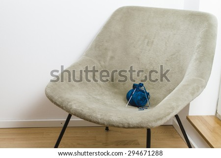 Armchair and blue knitting wool with needles