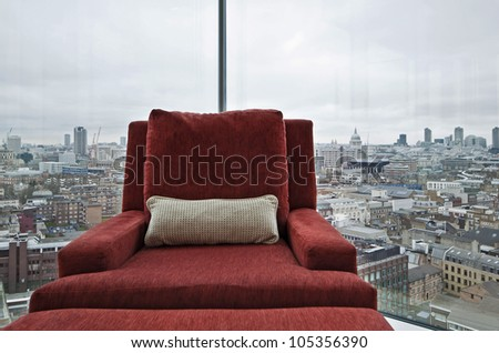 armchair in a floor to ceiling window with panoramic London views - stock photo